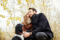 Free Couple Walking With Dog In The Park And Hugging. Autumn Walk In Stock Photo - 119743970