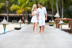 Couple Walking On Wooden Jetty Stock Photo