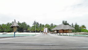 Couple Walking On Wooden Jetty. Couple walk towards camera position and along wooden jetty.Shot on Canon 5d Mk2 with a frame rate of 30fps stock video footage