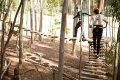 Couple walking on wooden obstacle bridge in the forest royalty free stock photos
