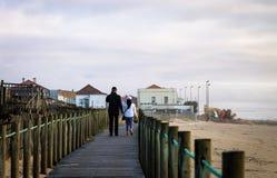 Couple Walks on Boardwalk at the Beach stock photos