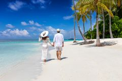 Couple walks down a tropical beach in the Maldives islands royalty free stock image