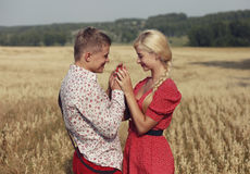 The couple walks through a field of ripe ears of wheat Stock Images