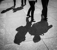Couple walks by the paved italian street contrast shadow image. In Milan, Italy Royalty Free Stock Images