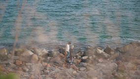 Couple walks on the rocks by the sea.  stock video footage