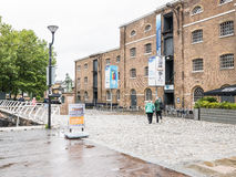 Couple walks tooward Museum of London, Docklands, on a rainy Aug. London, England, August 25, 2015: Couple walks toward Museum of London, Docklands, on a rainy royalty free stock images