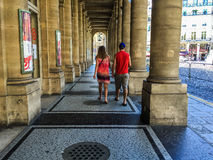 Couple walks under Comedie Francaise arcade in Paris Royalty Free Stock Photos
