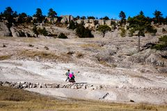 A couple walks through the Valley of the Monks in Creel, Mexico. CREEL, MEXICO - Jan 2016: A native Raramuri couple walks through the barren landscape of the Stock Images