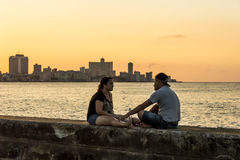 Couple on wall at Malecon in sunset Havana. Couple sitting on wall at Malecon in sunset. Havana, Cuba. Citizens of Havana is called Habaneros in Spanish Stock Images