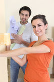 Couple wallpapering together Stock Image