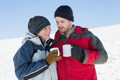 Couple in warm clothing with coffee cups on snow Stock Photo