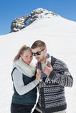 Couple in warm clothing in front of snowed hill Royalty Free Stock Photo