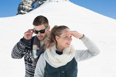 Couple in warm clothing in front of snowed hill Stock Photo
