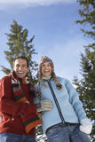 Couple In Warm Clothing Laughing Against Sky Royalty Free Stock Photo