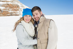 Couple in warm clothing on snow covered landscape Royalty Free Stock Photo