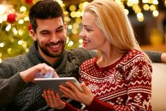 Couple in warm sweaters enjoying with tablet on Christmas stock photo