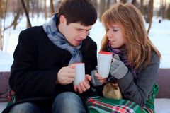 Couple warming themselves. Young beloved couple warming themselves in the winter park Royalty Free Stock Photos