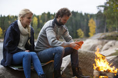Couple Warming Themselves By Bonfire Royalty Free Stock Images
