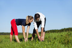 Couple warming up for exercise in summer Royalty Free Stock Photos