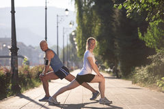 Couple warming up and stretching before jogging Stock Images
