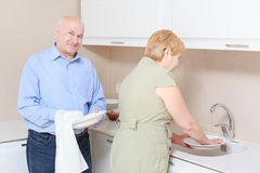 Couple washes dishes in the kitchen Stock Photography
