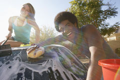 Couple Washing Car. Portrait of happy multiethnic couple washing car Stock Image