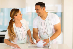 Couple washing dishes. Cheerful couple washing dishes together in the kitchen Royalty Free Stock Photo