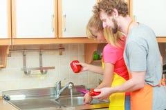 Couple washing fresh vegetables in kitchen Stock Photo