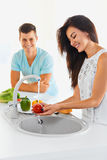 Couple washing vegetables in the kitchen. Focus on the woman. Stock Photo