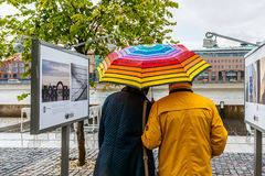 Couple watch photos in the rain Royalty Free Stock Photo