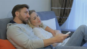 Couple watches TV at home. Attractive caucasian couple watching TV at home. Lovely couple lying embracing on the couch. Pretty blond woman lying on the man`s