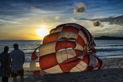 A couple watchig parachute by sunset Stock Photos