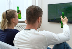 Couple watching American football. Stock Photography