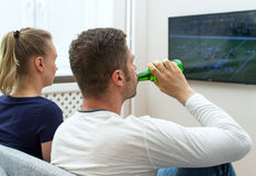 Couple watching American football. Royalty Free Stock Photos