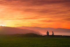 Couple watching beautiful sunset. On the coast stock images