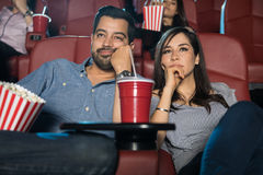 Couple watching a boring movie. Portrait of a young couple on a date watching a really boring movie at the cinema theater Stock Photo