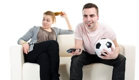 Couple watching football. Fascinated men watching football match and bored woman Stock Photo