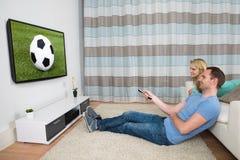 Couple watching football match Stock Photos