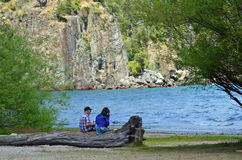 Couple watching the lake. Old man with his granddaughter drinking mate sitting on a tree branch near the lake Royalty Free Stock Images