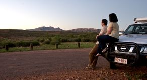 Couple Watching landscape from car in outback. Watching Sunset from viewing carpark Royalty Free Stock Photo
