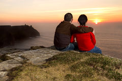 Couple watching lovely sunset. Loving Couple at sunset on irish Cliffs of Moher Royalty Free Stock Photo