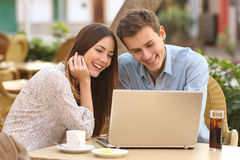 Couple watching media in a laptop in a restaurant Royalty Free Stock Photos