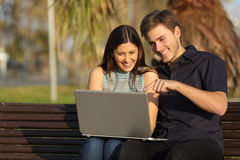Couple watching media in a laptop sitting on a bench Royalty Free Stock Images