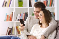 Couple watching media on a smart phone sitting at home. Happy couple watching media content on a smart phone sitting on a couch at home stock image