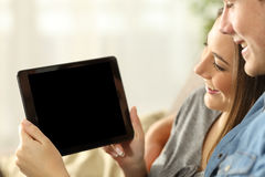 Couple watching media in a tablet showing screen. Close up of a happy couple watching media in a tablet and showing the blank screen sitting on a sofa in the Stock Images