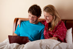 Couple watching the movie in bed Stock Photo