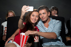 Couple watching movie at cinema and photographing themselves. A young couple watching a movie at a cinema and photographing themselves with a Smartphone Stock Photos