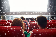 Couple watching movie in theater or cinema. Cinema, entertainment, leisure and people concept - couple watching movie in theater from back over snowflakes Royalty Free Stock Photography
