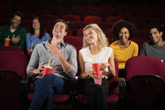 Couple watching movie in theatre. Happy couple watching movie in theatre Royalty Free Stock Photography
