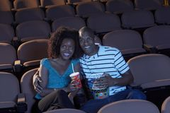 Couple Watching Movie Together. Happy African American couple watching movie together with popcorn and drink Stock Photography